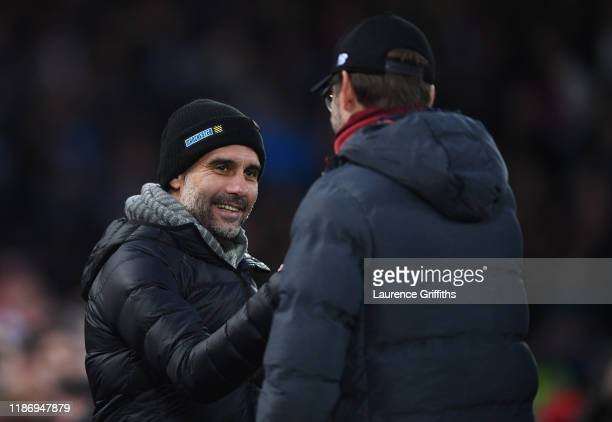 Josep Guardiola of Manchester City is greeted by Jurgen Klopp of Liverpool looks on with ta smile ahead of the Premier League match between Liverpool...