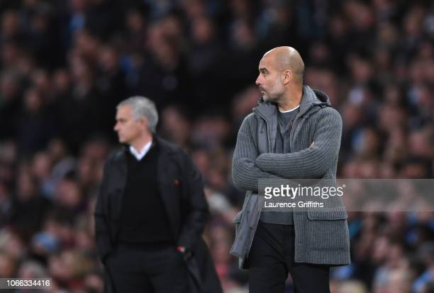 Josep Guardiola of Manchester City looks on in front of Jose Mourinho fo Manchester United during the Premier League match between Manchester City...