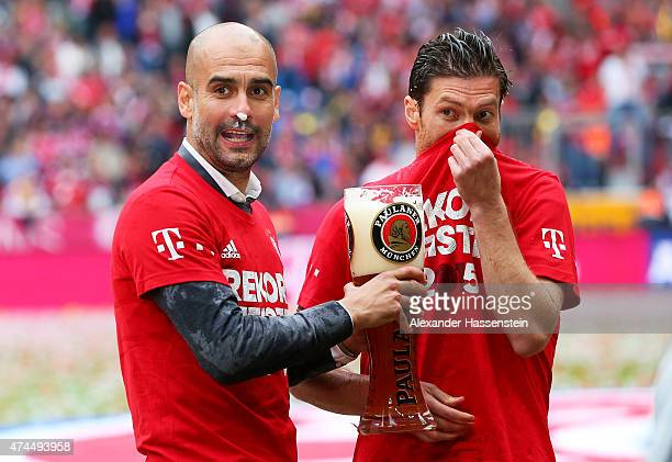 Josep Guardiola the head coach of Bayern Muenchen and Xabi Alonso of Bayern Muenchen celebrate winning the league following the Bundesliga match...