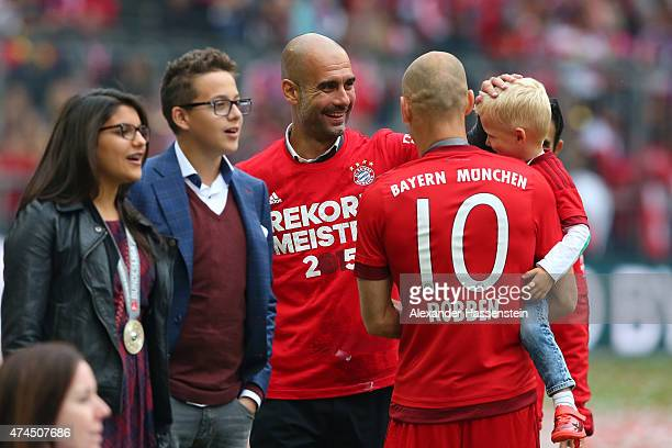 Josep Guardiola the head coach of Bayern Muenchen celebrates with Arjen Robben of Bayern Muenchen and his son after winning the league during the...