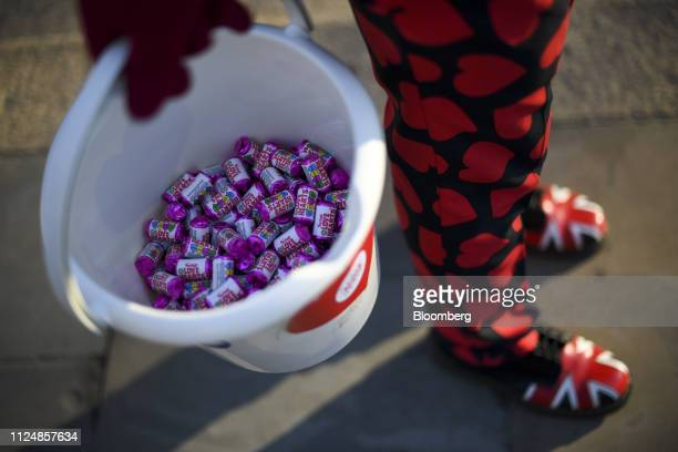 Joseph Afrane UK opposition Labour Party supporter holds a bucket of Love Heart sweets as he demonstrates in support of Brexit near the House of...