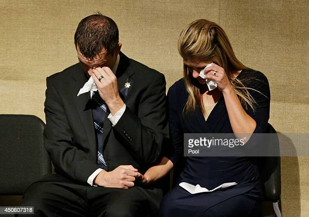 Joseph Beck and Elizabeth Krmpotich wipe tears from their eyes during a memorial service for their brother Las Vegas Metropolitan Police Officer Alyn...