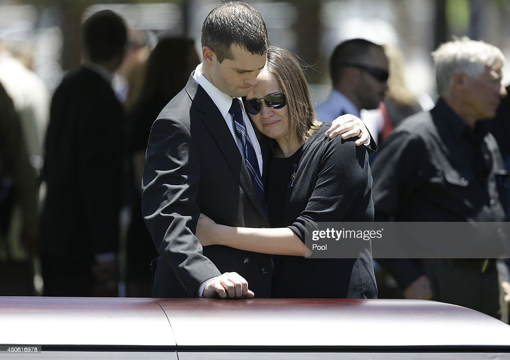 Joseph Beck, left, embraces an unidentified woman as they stand over the casket of Beck's brother Las Vegas Metropolitan Police Officer Alyn Beck during a memorial at The Smith Center for the Performing Arts Saturday, on June 14, 2014 in Las Vegas, Nevada. Police said Beck and Officer Igor Soldo were shot and killed on June 8 at a restaurant by Jerad Miller and his wife Amanda Miller. Police said the Millers then went into a nearby Wal-Mart where Amanda Miller killed Joseph Wilcox before police killed Jerad Miller and Amanda Miller killed herself.