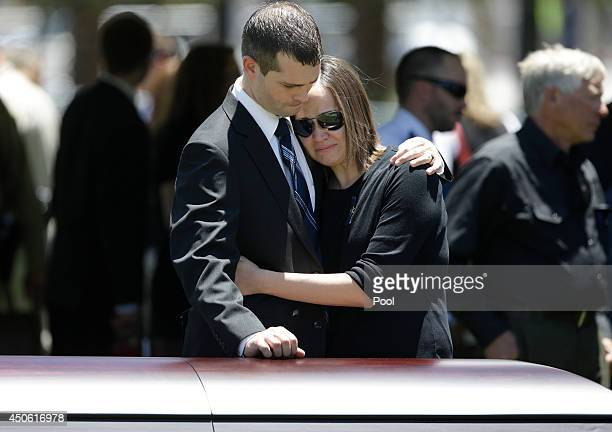 Joseph Beck left embraces an unidentified woman as they stand over the casket of Beck's brother Las Vegas Metropolitan Police Officer Alyn Beck...