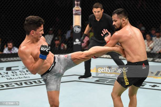 Joseph Benavidez kicks Jussier Formiga of Brazil in their flyweight bout during the UFC Fight Night event at the Target Center on June 29 2019 in...