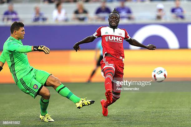 Joseph Bendik of Orlando City SC kicks the ball in front of Kei Kamara of New England Revolution during a MLS soccer match at Camping World Stadium...