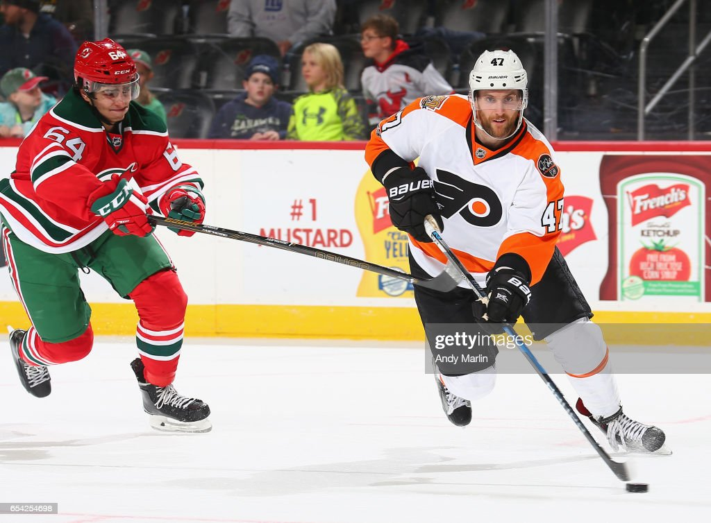 Joseph Blandisi #64 of the New Jersey Devils stick checks Andrew MacDonald #47 of the Philadelphia Flyers as he plays the puck during the game at Prudential Center on March 16, 2017 in Newark, New Jersey.