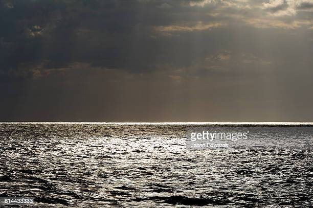 Sunrays pierce ominous storm clouds over a calm tropical ocean.