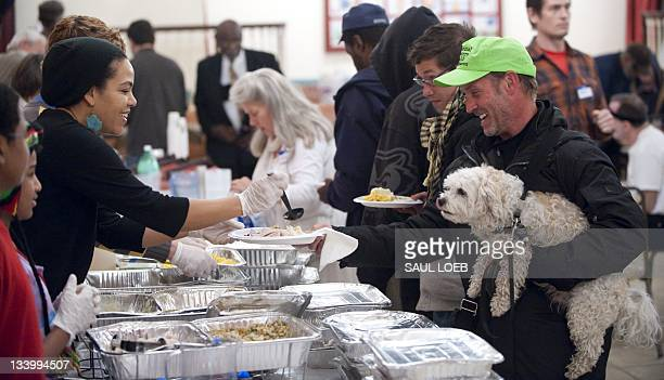 Joseph Bratcher and his dog Wally receive a Thanksgiving holiday meal provided for Occupy DC demonstrators from volunteers at New York Avenue...