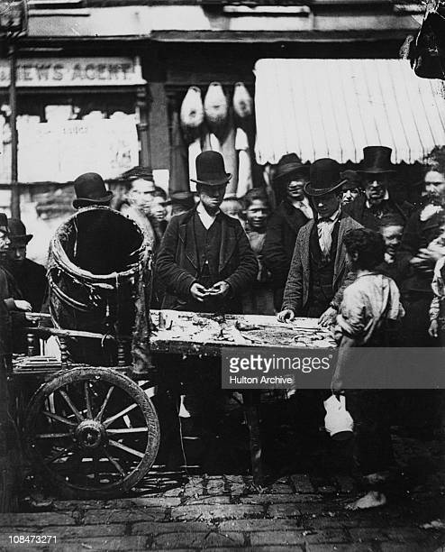 Joseph Carney at his fish stall in the market between Seven Dials and Five Dials in St Giles London circa 1877 Leaning on a lamppost at the far left...