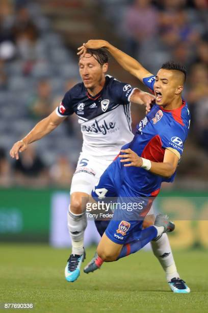 Joseph Champness of the Jets contests the ball with Mark Milligan of the Victory during the round eight ALeague match between the Newcastle Jets and...