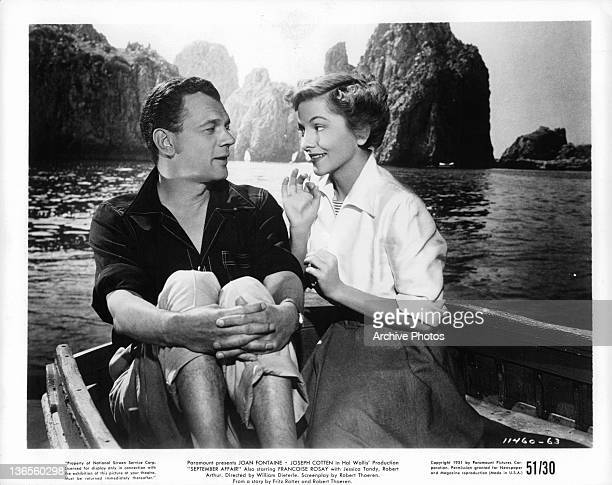 Joseph Cotten and Joan Fontaine sitting in a boat on the water together in a scene from the film 'September Affair' 1950