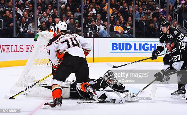 Joseph Cramarossa of the Anaheim Ducks carries the puck around the net against Peter Budaj Alec Martinez and Nic Dowd of the Los Angeles Kings on...