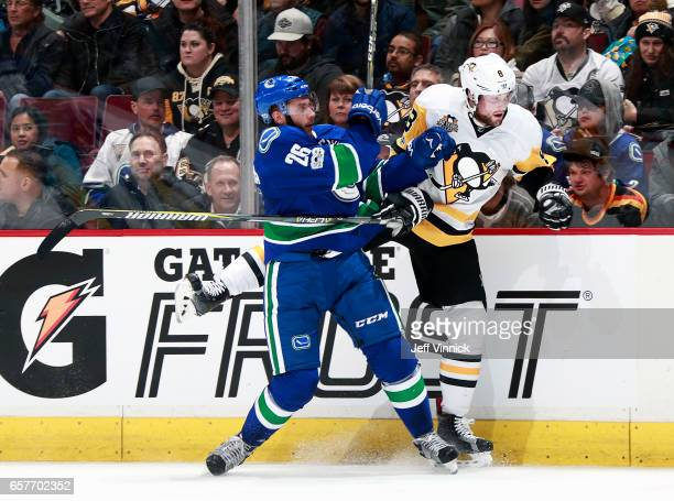 Joseph Cramarossa of the Vancouver Canucks checks Brian Dumoulin of the Pittsburgh Penguins during their NHL game at Rogers Arena March 11 2017 in...