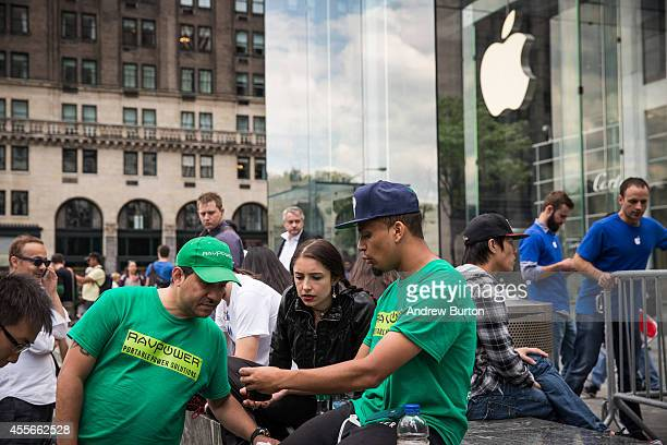Joseph Cruz shows his phone to Moon Ray an another man while waiting in line for the iPhone 6 to go on sale outside the Apple store on Fifth Avenue...
