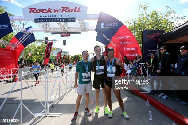 Joseph Darda Bennett Grimes and Masanori Okabe pose at the finish line after placing as the top three for the Men's Marathon during the St Jude Rock...