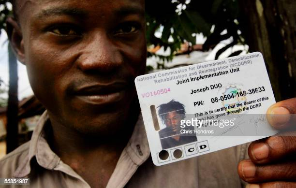 Joseph Duo a former Liberian government soldier displays a card given to him and thousands of other former combatants in the Liberian civil war...