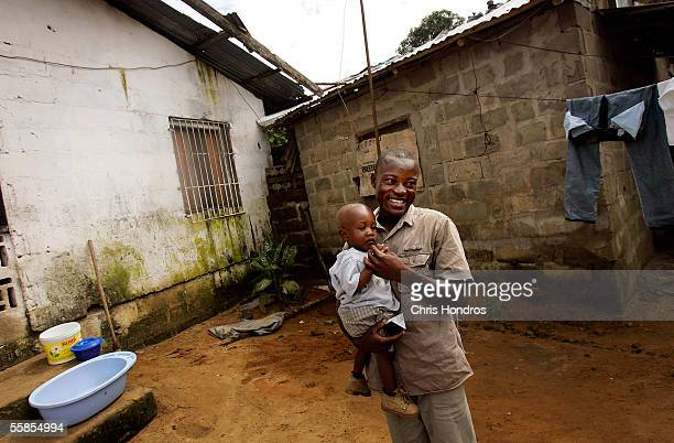 Joseph Duo a former Liberian government soldier plays with his son Kuku October 5 2005 in Monrovia Liberia A picture of Duo jumping into the air in...