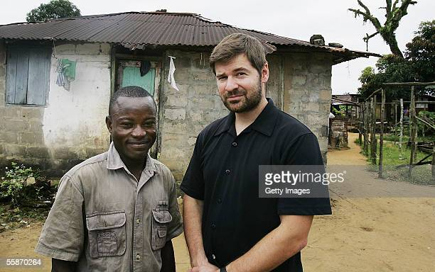 Joseph Duo a former Liberian government soldier poses with photographer Chris Hondros at his home October 5 2005 in Monrovia Liberia A picture of Duo...