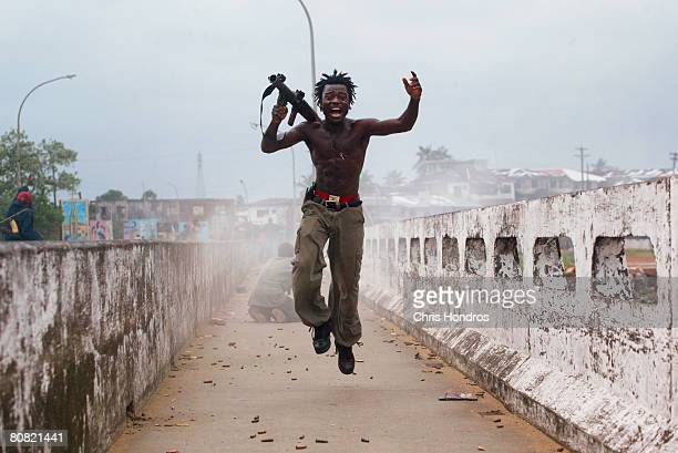 Joseph Duo, a Liberian militia commander loyal to the government, exults after firing a rocket-propelled grenade at rebel forces at a key strategic...