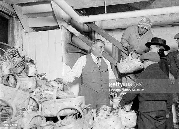 Joseph Esposito reputed gangster hands out baskets of food to people at an unidentified Chicago location 1926 Esposito was a corrupt politician who...