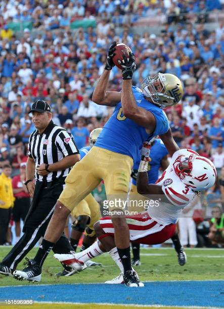 Joseph Fauria of the UCLA Bruins catches a four yard touchdown pass in the end zone in the second quarter over defensive back Daimion Stafford of the...