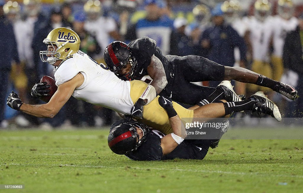 Joseph Fauria #8 of the UCLA Bruins is tackled by Ed Reynolds #29 and Jordan Richards #8 of the Stanford Cardinal during the Pac-12 Championship game at Stanford Stadium on November 30, 2012 in Stanford, California.