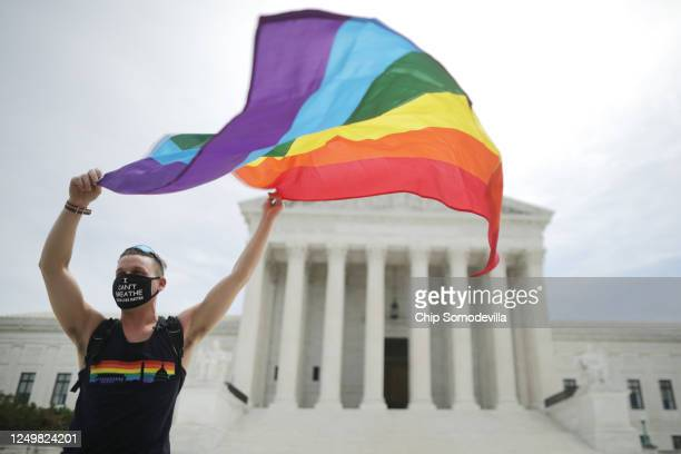 Joseph Fons holding a Pride Flag in front of the U.S. Supreme Court building after the court ruled that LGBTQ people can not be disciplined or fired...