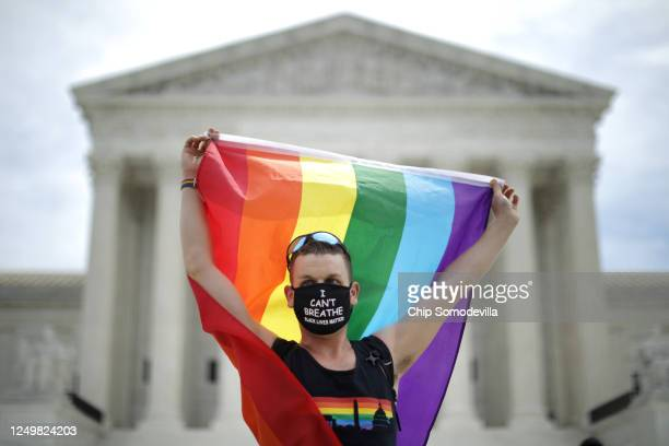 Joseph Fons holding a Pride Flag, stands in front of the U.S. Supreme Court building after the court ruled that LGBTQ people can not be disciplined...