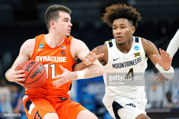 Joseph Girard III of the Syracuse Orange controls the ball against Miles McBride of the West Virginia Mountaineers in the second half of their second...