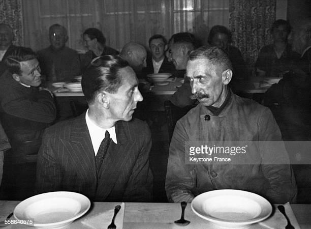 Joseph Goebbels discute avec un ouvrier du groupement industriel AEG au réfectoire du personnel en octobre 1938 en Allemagne