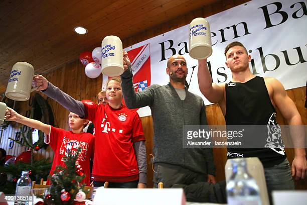 Joseph Guardiola head coach of FC Bayern Muenchen competes in a typical Bavarian feat to see who can hold a one litre beer mug in the air the longest...