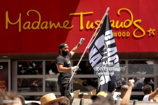 HOLLYWOOD CA JUNE 14 2020 Joseph Harold waves a Black Lives Matter flag while joining thousands who participate in the All Black Lives Matter...