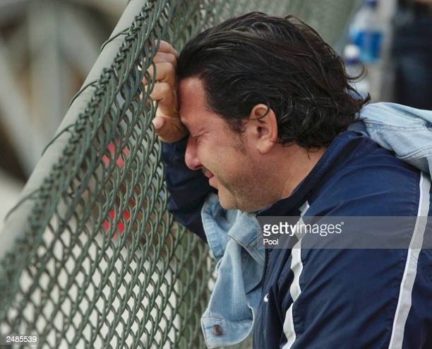 Joseph Irizarry of Seacaucus, New Jersey, who lost his brother-in-law Ruben Esquilin Jr. In the World Trade Center attacks, cries on a fence...