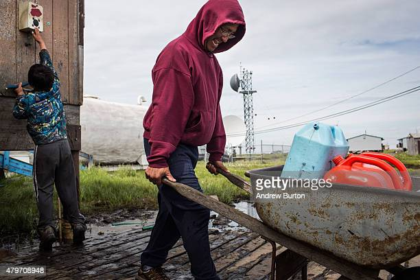 Joseph John Jr collects fresh water for his family at the fresh water storage tank one of the only places to get fresh water in town on July 5 2015...