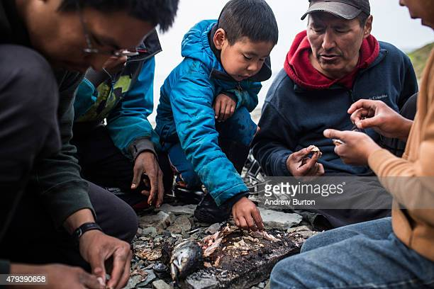 Joseph John Jr eats a freshly caught salmon with his sons and friends while waiting for the tide to come in after a day of salmon fishing on July 1...