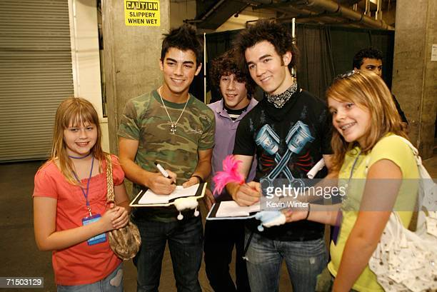 Joseph Jonas, Nicholas Jonas and Kevin Jonas of The Jonas Brothers sign autographs backstage at the Radio Disney Totally 10 Birthday Concert held at...
