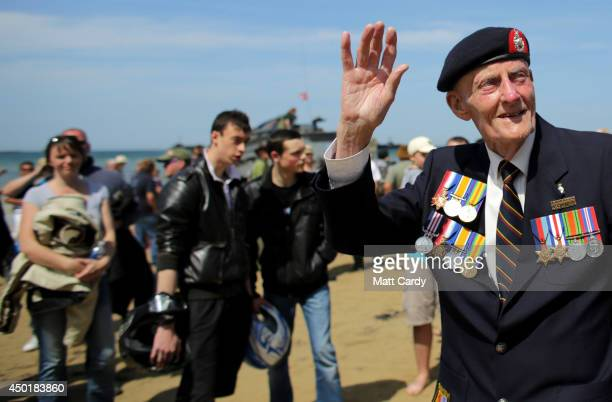 Joseph Kellsey who was in the Royal Marines on Sword Beach on DDay waves as people who applauded him as he walked on the beach at...