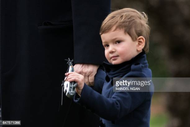 Joseph Kushner holding a toy Marine One walks with his grandfather US President Donald Trump as they make their way to board Marine One on the South...