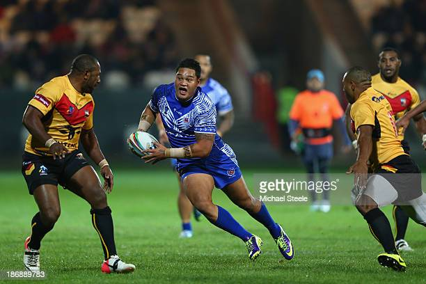 Joseph Leilua of Samoa runs at Menzie Yere and Josiah Abavu f Papua New Guinea during the Rugby League World Cup Group B match between Papua New...