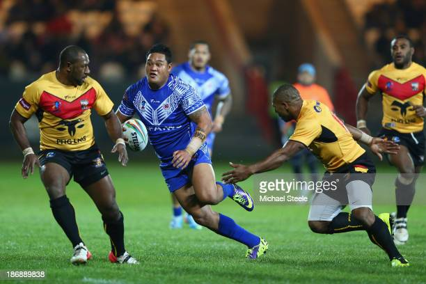 Joseph Leilua of Samoa runs at Menzie Yere and Josiah Abavu of Papua New Guinea during the Rugby League World Cup Group B match between Papua New...