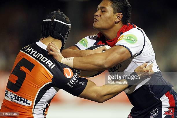 Joseph Leilua of the Roosters is tackled by Beau Ryan of the Tigers during the round 20 NRL match between the Wests Tigers and the Sydney Roosters at...
