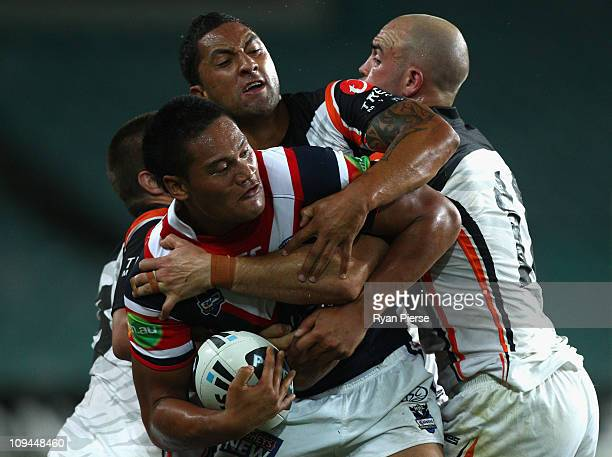 Joseph Leilua of the Roosters is tackled by Benji Marshall and Liam Fulton of the Tigers during the Foundation Cup NRL trial match between the Sydney...