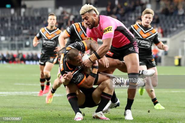 Joseph Leilua of the Tigers is tackled during the round eight NRL match between the Wests Tigers and the Penrith Panthers at Bankwest Stadium on July...