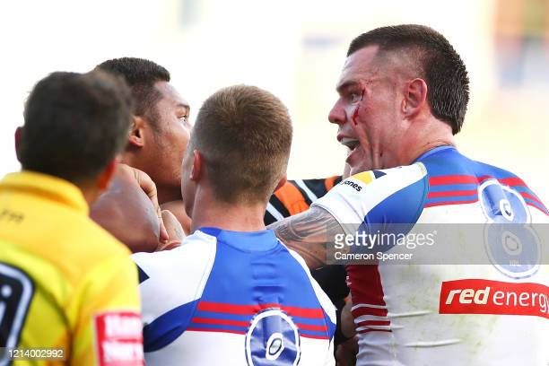 Joseph Leilua of the Wests Tigers and David Klemmer of the Knights scuffle as they exchange words during the round 2 NRL match between the Wests...