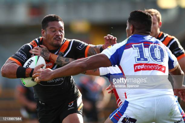 Joseph Leilua of the Wests Tigers is tackled during the round 2 NRL match between the Wests Tigers and the Newcastle Knights at Leichhardt Oval on...