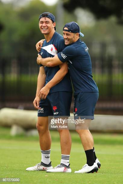 Joseph Manu and Cooper Cronk share a laugh during a Sydney Roosters NRL training session at Kippax Lake on March 5 2018 in Sydney Australia