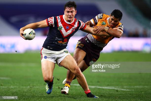 Joseph Manu of the Roosters fends off Jordan Kahu of the Broncos during the round 24 NRL match between the Sydney Roosters and the Brisbane Broncos...