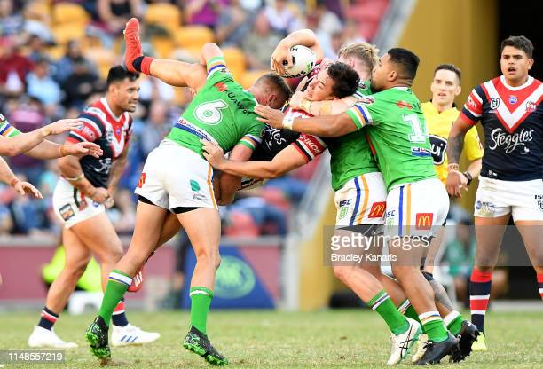 Joseph Manu of the Roosters is upended in the tackle during the round nine NRL match between the Sydney Roosters and the Canberra Raiders at Suncorp...
