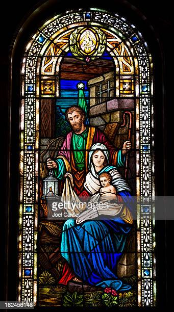 joseph, mary, and baby jesus in stained glass - manger stock photos and pictures